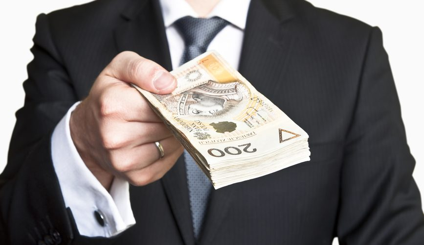 Businessman wearing suit and tie handing a lot of Polish money