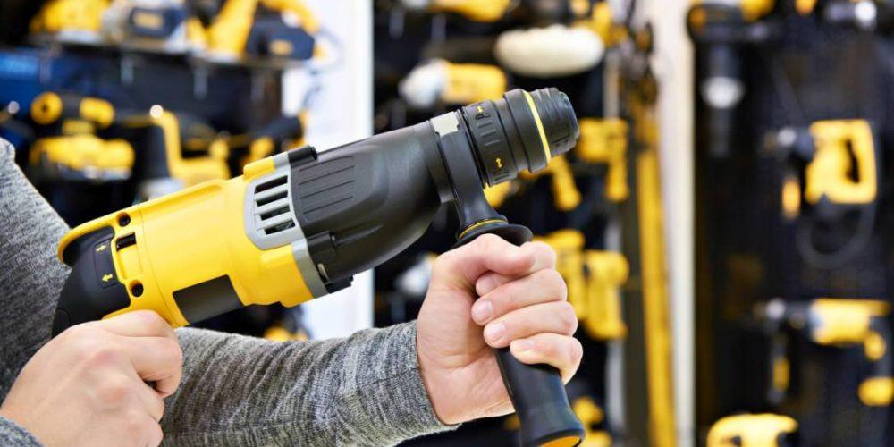 Hammer drill in man's hands closeup