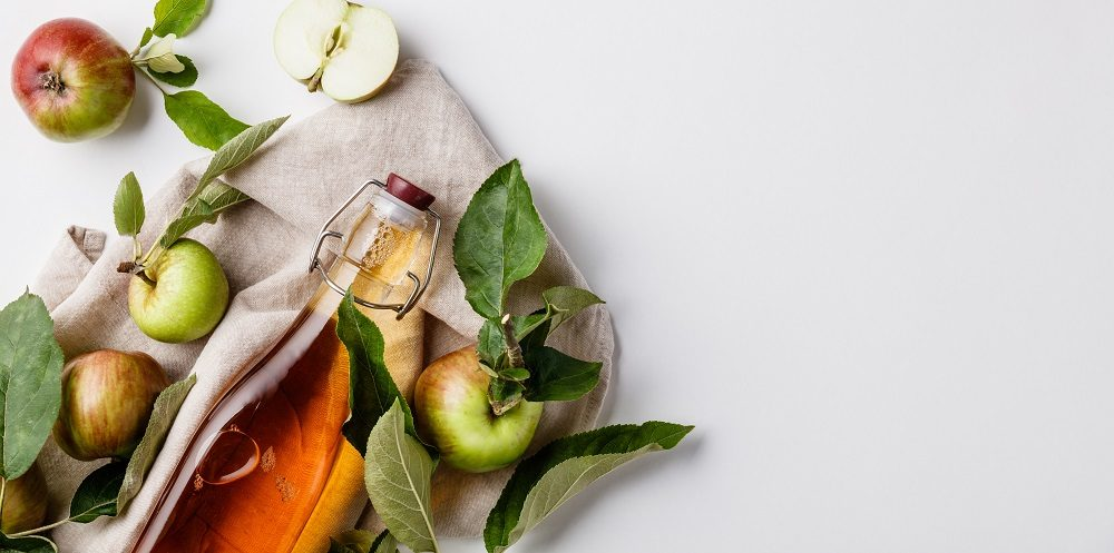 Apple cider vinegar and fresh apples, flat lay, space for your text. Fermented food concept